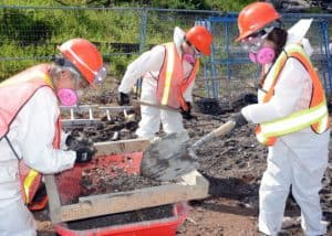 Three Samaritan's Purse volunteers dig through ash